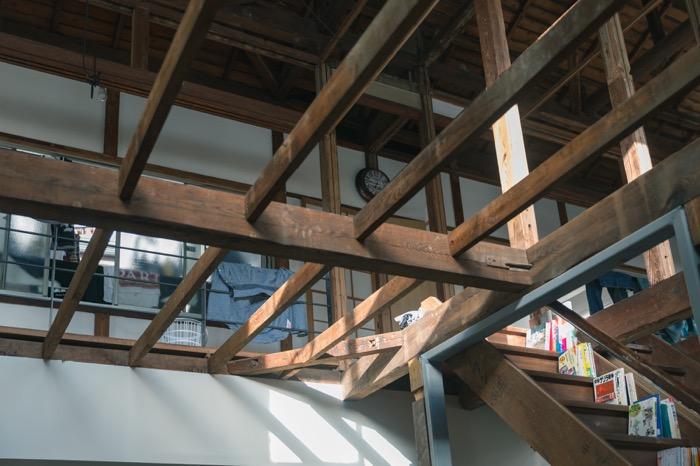 2軒長屋をつなげた室内の真ん中に走る2つの階段は本棚に